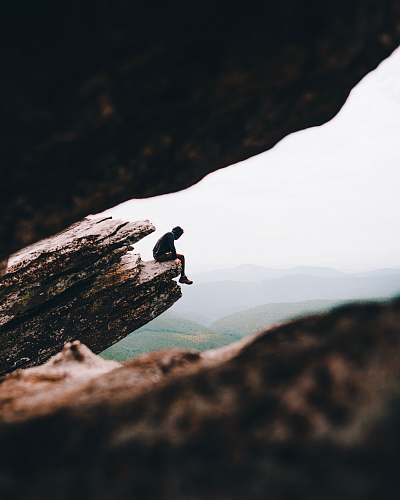 adventure selective focus photography of person sitting on cliff during daytime leisure activities