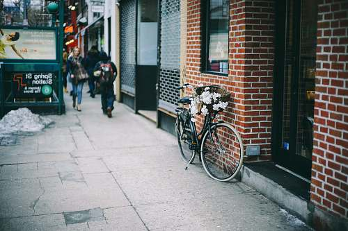 sidewalk black city bicycle parked beside brown concrete brick wall bicycle