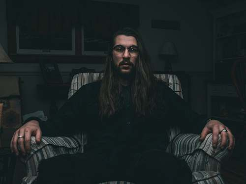 human man in black dress shirt sitting on sofa chair person