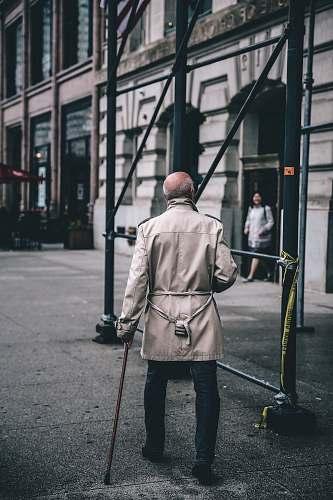 human man walking near scaffolding during daytime person