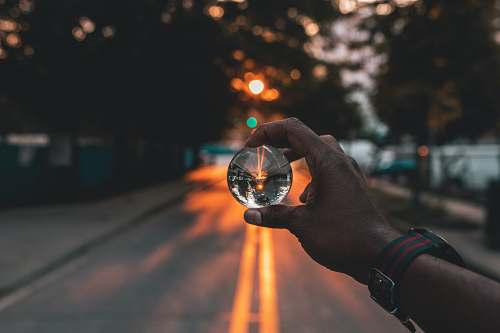 human person holding snow globe under sunset person