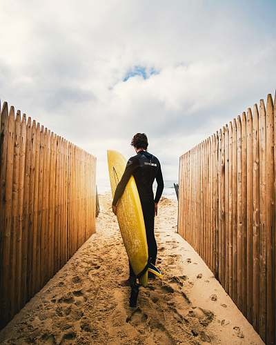 human person standing between privacy fences while holding yellow surfboard during daytime person