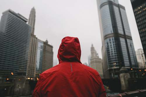 human person wearing red hoodie standing in front of high rise buildings person