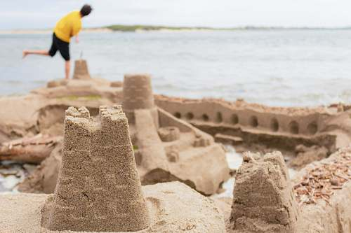 person selective focus photography of sand castle near man standing on seashore human