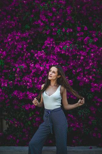human smiling woman holding her hair in front of purple flowers during daytime person