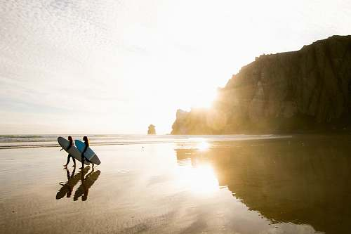 human two people carrying surfboards while walking on seashore person