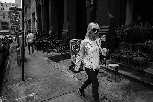 person woman walking on pathway near concrete building black-and-white