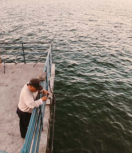 people man holding black fishing rod standing on boat deck at daytime fishing