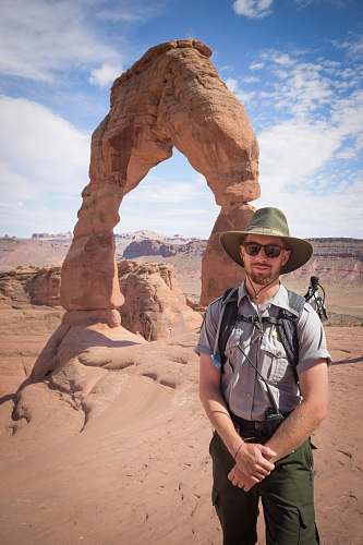 human man standing near Delicate Arch people