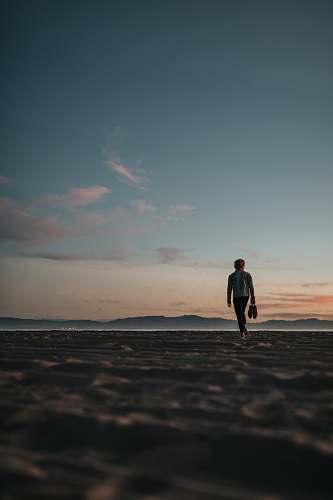 human man walking on sand while holding his footwears people