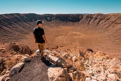 mountain man wearing black shirt standing on rock formation during daytime human