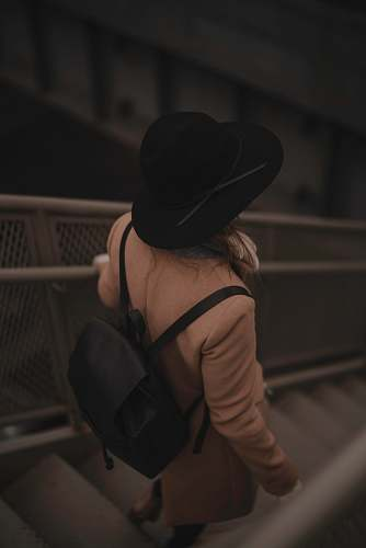 people person carrying black backpack while walking downards of stair hat