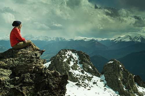 outdoors person sitting on rock across snow covered mountain under cloudy sky mountain