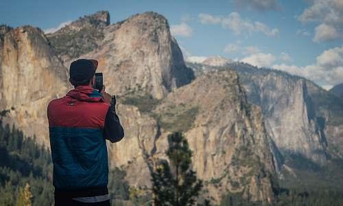 people person taking photo of mountains during daytime mountain range