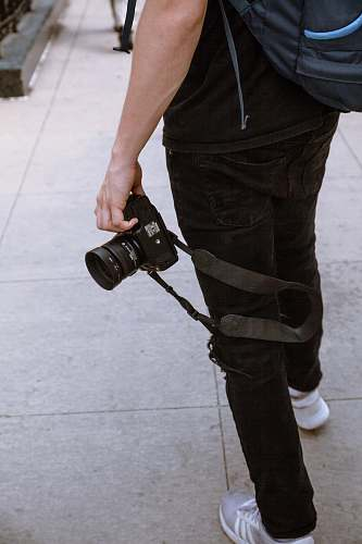 people person wearing black jeans holding black DSLR camera human