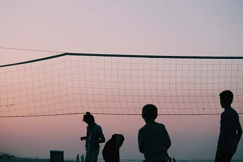 human silhouette of four people playing volleyball during nighttime people