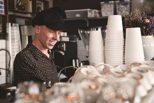 human smiling man beside cups people