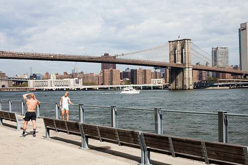 human two men taking picture in front of Brooklyn Bridge people
