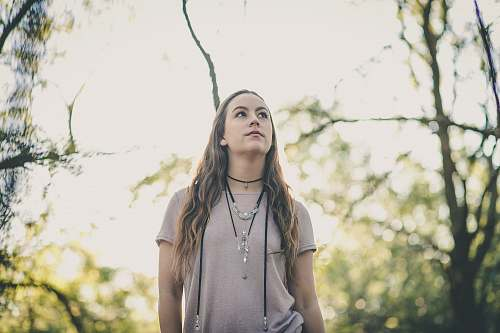 people woman in gray t-shirt standing between tree branches human