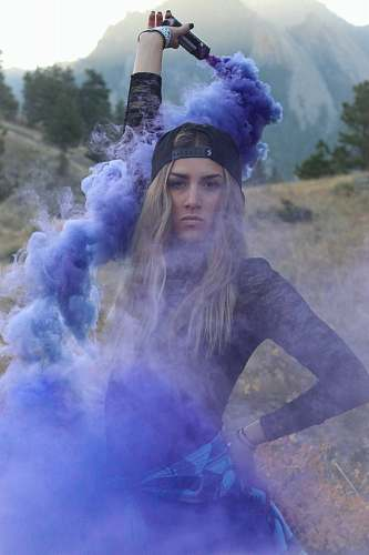 human woman raising purple smoke bomb during daytime people