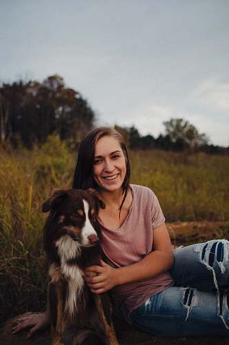 human woman sitting beside a black and white dog dog