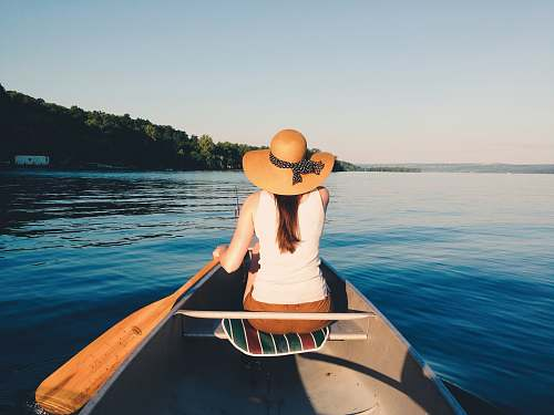 boat woman wearing sunhat riding boat on body of water canoe