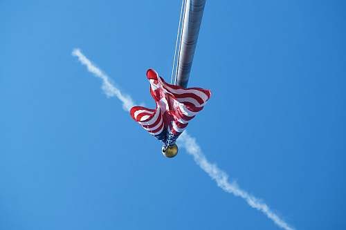 human worm's-eye view photography of USA flag in pole people