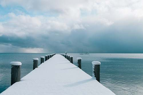 lake tahoe brown wooden dock covered with snow and body of water snow