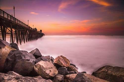 ocean low-angle photography of rocks near bridge coast