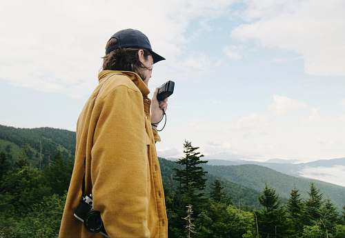 tree man wearing yellow coat with camera human