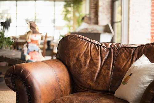 human white throw pillow on brown leather armchair person