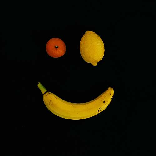 food yellow lime, orange fruit, and yellow banana with smile formation fruit