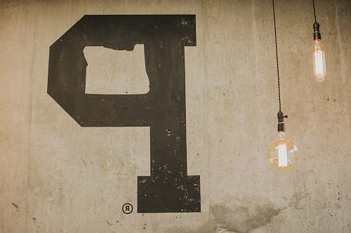 text two pendant lamp near beige wall with P letter alphabet
