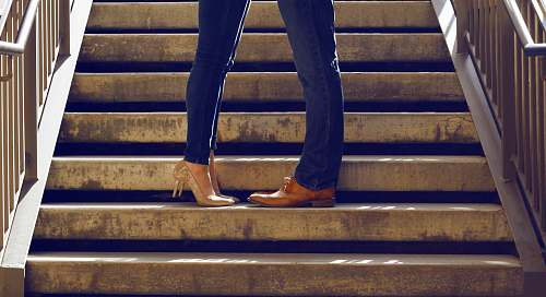 couple two person wearing blue jeans standing on gray concrete stair handrail