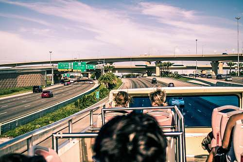 freeway group of people sitting on top of double-decker bus overpass