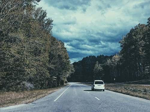 asphalt white vehicle on road near trees during daytime tarmac