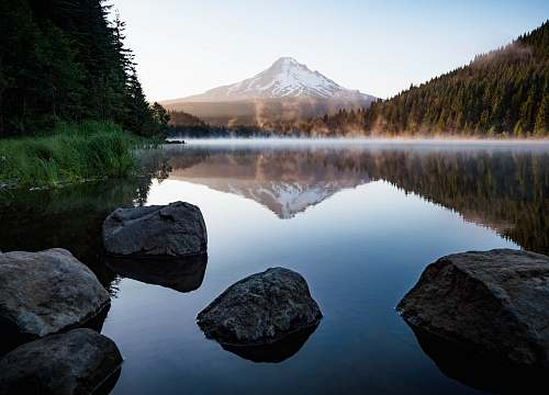 water calm body of water with rocks near trees and mountain tree