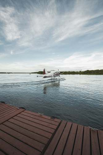 transportation white and red airplane taking off from water seaplane