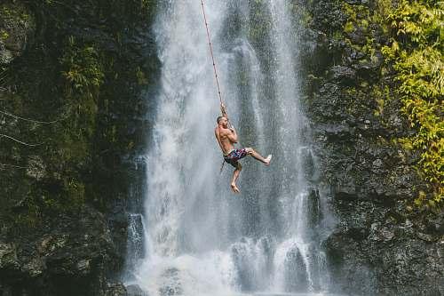 adventure man hanging on rope near waterfalls during daytime bungee