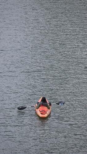 kayak person on kayak on body of water boat