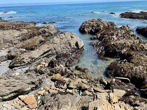 promontory black rock formation beside sea rock