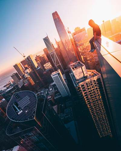 architecture person sitting on top of building during daytime urban