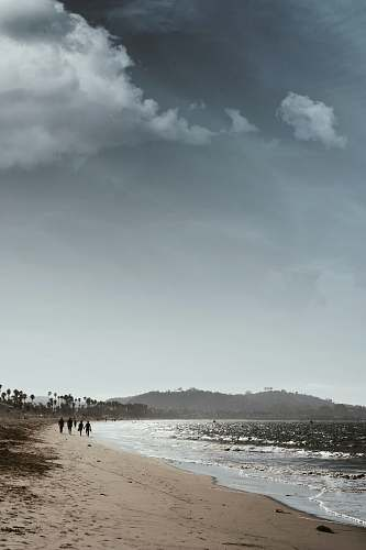 beach people walking near seashore during daytime grey