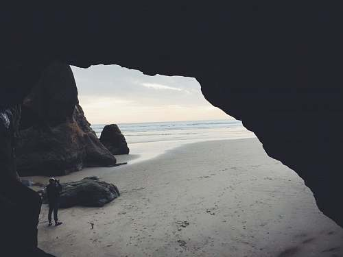 cave person taking picture beside cave ocean