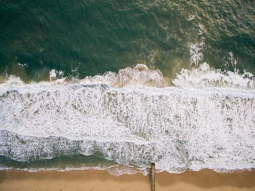 water top view photography of brown beach sand with teal ocean water during daytime ocean