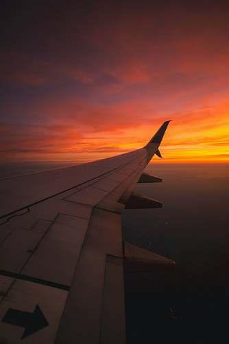 sunset bird's eye view photography of airplane wing sunrise
