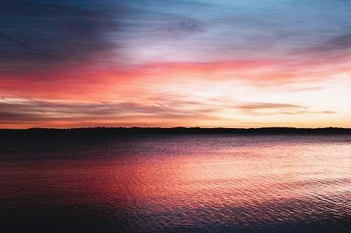 sunset calm body of water during sunset photo sunrise