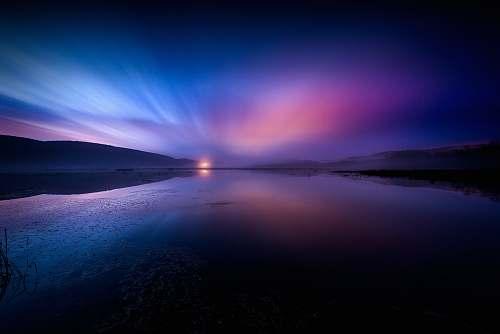 dusk landscape photography of body of water under dramatic sky sunrise