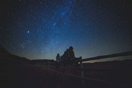 night several women sitting on fence watching milky way astronomy