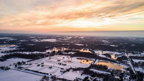 winter aerial photography of snow covered area under white cloudy skies golden hour photography mantua
